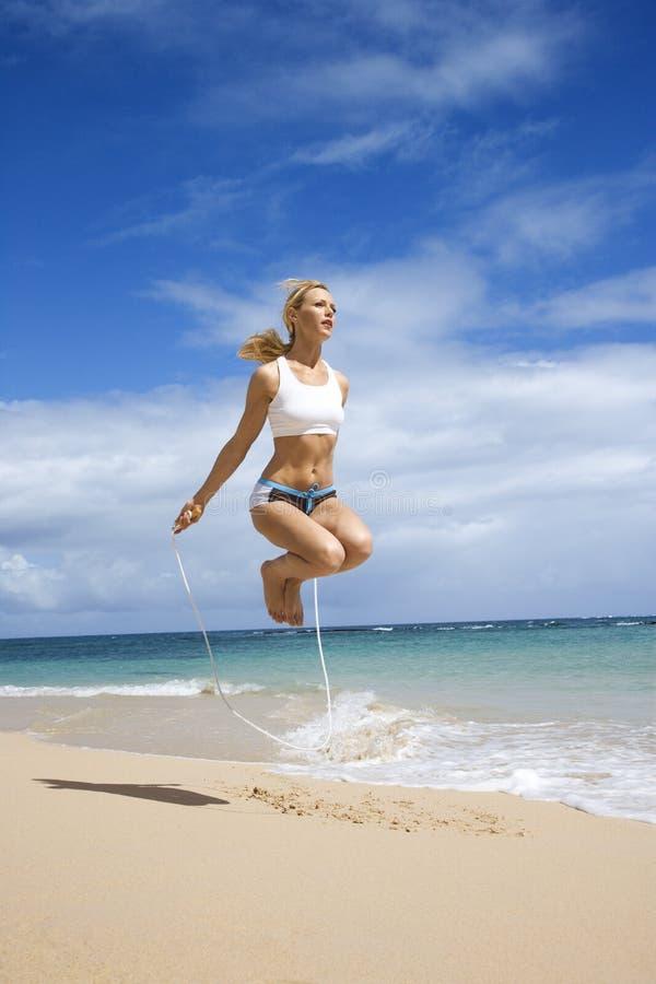 De touwtjespringen van de vrouw op strand. stock foto's