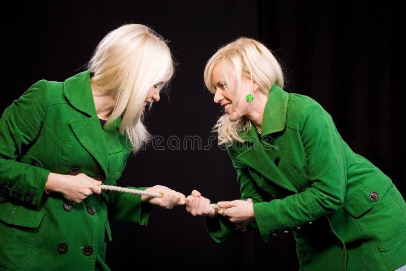 De touwtrekwedstrijd van zusters stock afbeeldingen