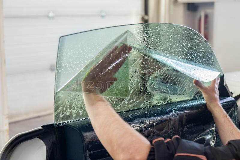 De tovenaar voor het installeren van extra materiaal plakt een tintfilm op het zij voorglas van de auto en vlakt het met de hand  stock afbeeldingen