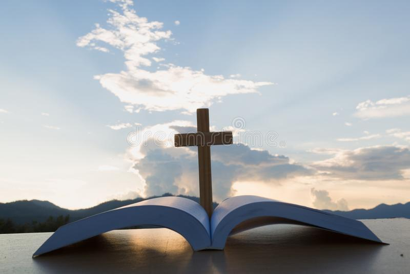 De trä korsar den över öppnade bibeln på trätabellen, härlig himmelbakgrund arkivfoto