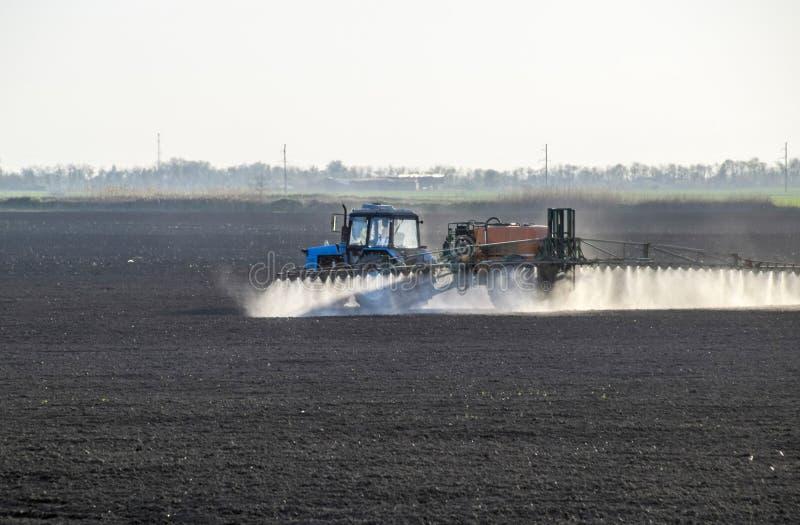 De tractor bespoot herbiciden op het gebied Chemie in agricu stock fotografie