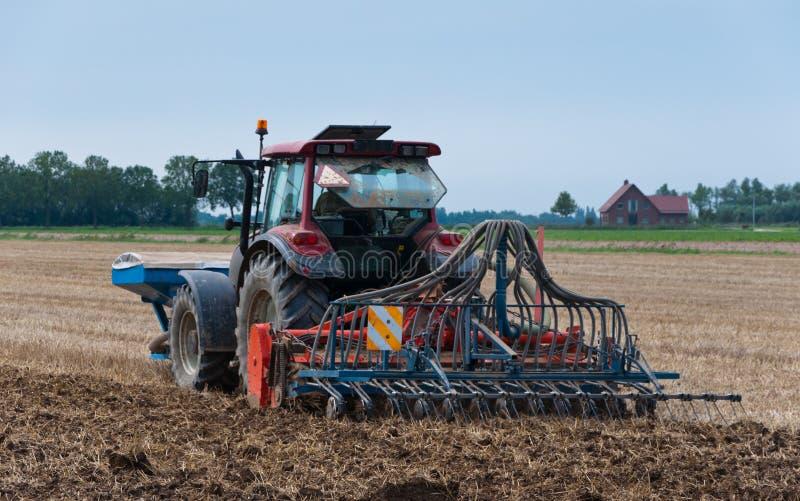 De tractor en de zaaimachine van het landbouwbedrijf van de rug stock afbeeldingen