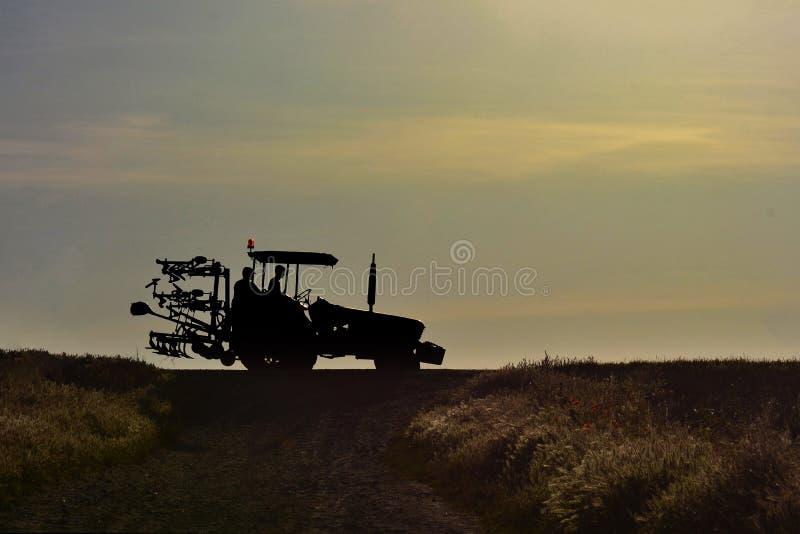 De tractor met landbouwerssilhouetten gaat in zonsondergang naar huis stock afbeeldingen