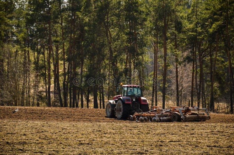 De tractor ploegt het gebied De lente, het begin van het het planten seizoen Grote tractorritten op het gebied stock afbeeldingen