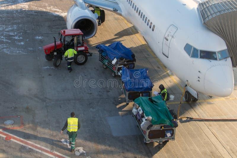 De tractor trekt de karren met bagage aan het luchtvliegtuig stock fotografie