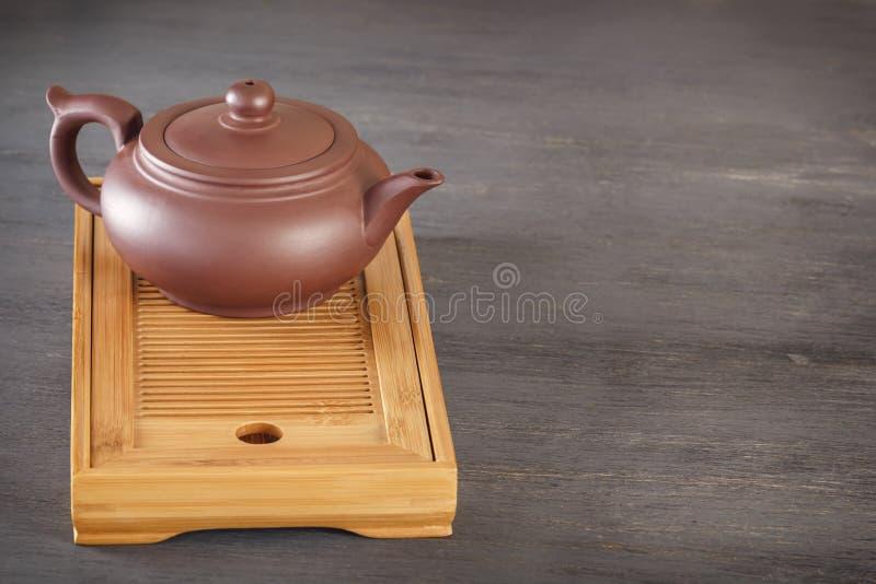 De traditionele Aziatische ceramische theepot bevindt zich op een speciaal houten theedienblad op een grijze lijst stock foto