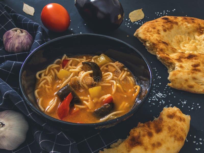 De traditionele Aziatische schotel is Lagman Aziatische flatbread lavash, knoflook, tomaten, noedels, Spaanse peper, aubergine, a stock fotografie