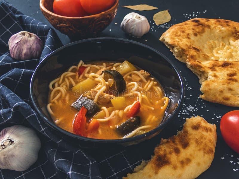 De traditionele Aziatische schotel is Lagman Aziatische flatbread lavash, knoflook, tomaten, noedels, Spaanse peper, aubergine, a royalty-vrije stock afbeeldingen