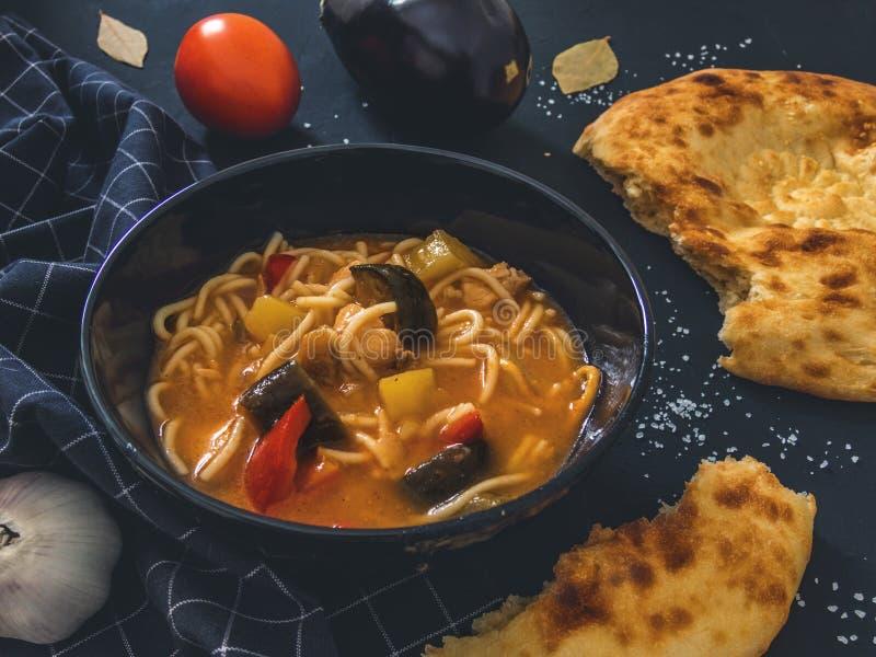 De traditionele Aziatische schotel is Lagman Aziatische flatbread lavash, knoflook, tomaten, noedels, Spaanse peper, aubergine, a stock afbeeldingen
