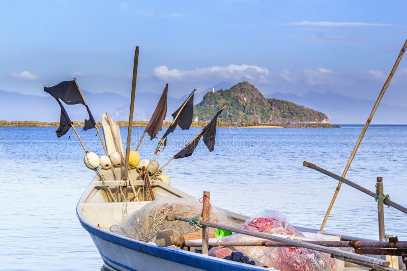 De traditionele Aziatische vissersboot plaatst netten voor visserij in het overzees tegen een blauwe hemel met wolken royalty-vrije stock foto's