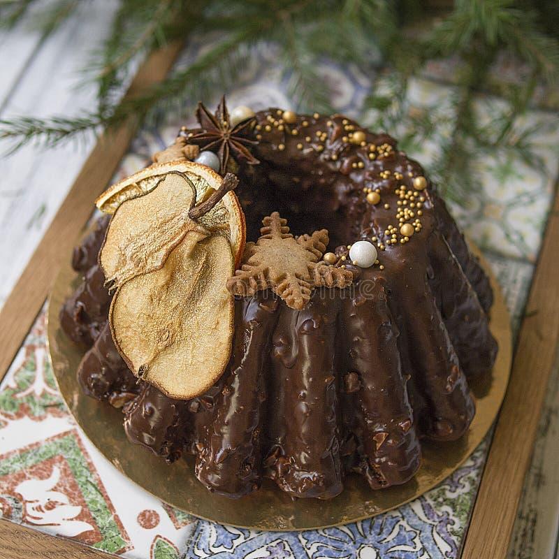 De de traditionele die cake of pudding van het Kerstmisfruit in chocoladeglans met koekjes, peren en sinaasappelen op feestelijke stock foto's