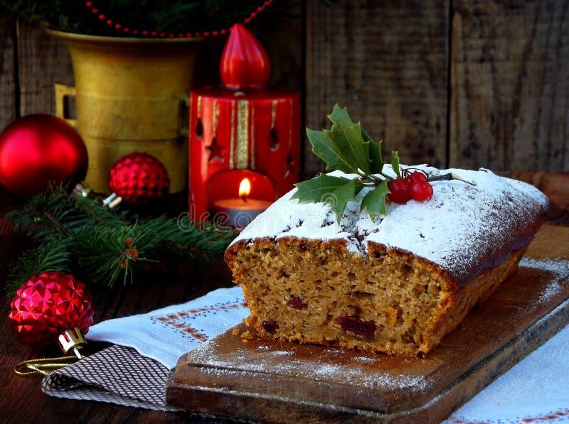 De traditionele die cake van het Kerstmisfruit met gepoederde suiker en mas decoratie, kaars wordt verfraaid De ruimte van het ex stock fotografie