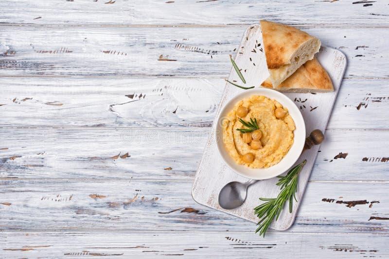 De traditionele eigengemaakte snack van kikkererwtenhummus met kruid van rozemarijn en pittabrood stock fotografie