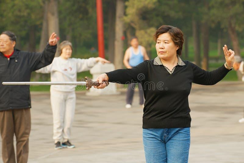De traditionele gymnastiek van damepraktijken met een zwaard in Jingshan-Park in Peking, China royalty-vrije stock foto's