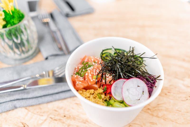 De traditionele Hawaiiaanse kom van de schotelpor met vork Hawaiiaanse zalmvissen met rijst, radijs, komkommer, tomaat, sesamzade stock foto