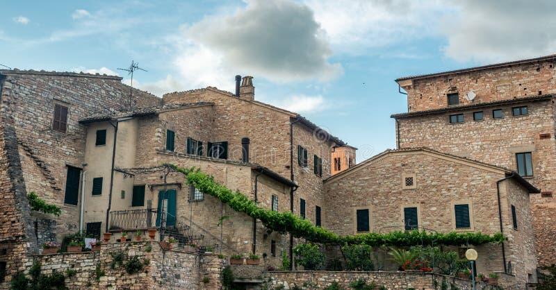 De traditionele Italiaanse middeleeuwse bouw met huizen in het historische centrum van mooie stad van Spello, in Umbria Region, I stock foto