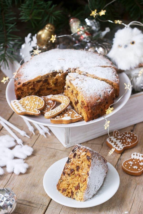 De traditionele Kerstmisvruchtencake op de achtergrond van een doos met Kerstmisspeelgoed en spar vertakt zich royalty-vrije stock foto