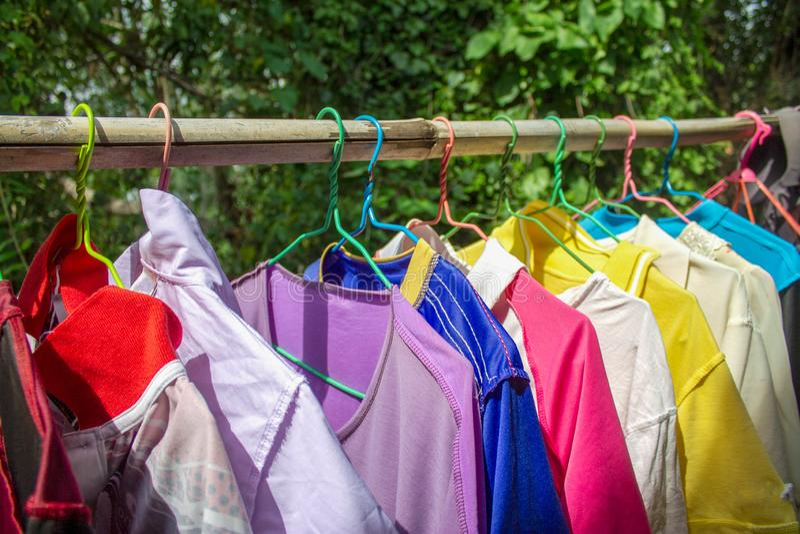 De Traditionele kleren in hanger hangen op een bamboeplank Het Overhemd hangt op bamboeplank stock afbeeldingen