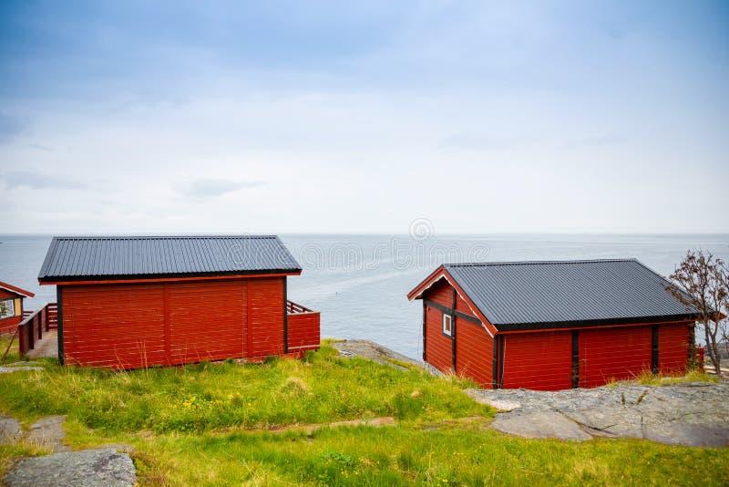 De traditionele rode het kamperen huizen met een mooie overzees bekijken naast dorp A binnen lofoten, Noorwegen stock foto