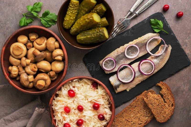 De traditionele Russische snacks, zuurkool met Amerikaanse veenbessen, haringen, ingelegde komkommers, legden paddestoelen en rog royalty-vrije stock afbeeldingen