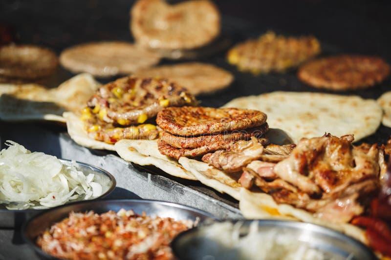 De traditionele Servische hamburger of pljeskavica van het straatvoedsel, flatbread en vlees stock afbeelding