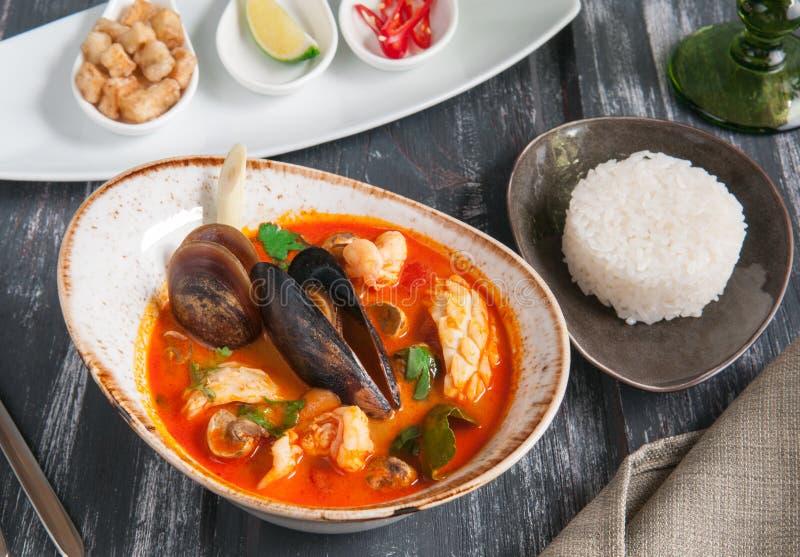 De traditionele soep Tom Yam van Thailand Met garnalen, mosselen, kammosselvlees, rijst en hete kruiden stock foto's