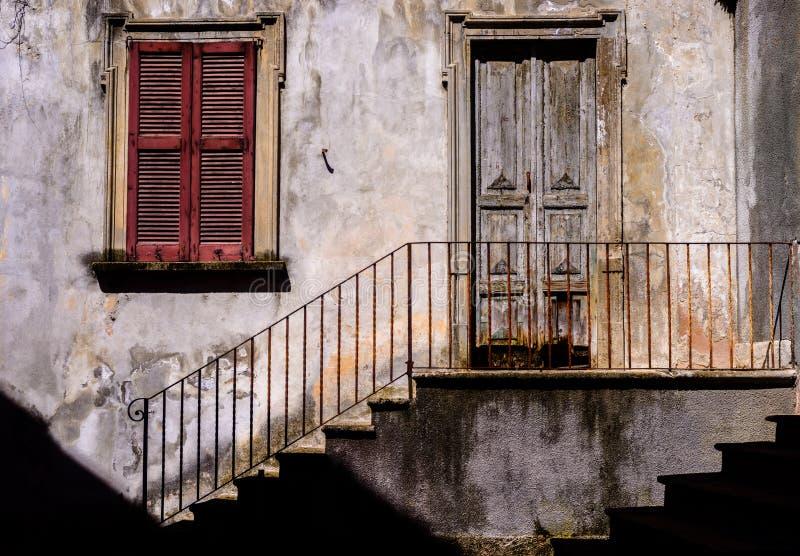 De traditionele sun-lit rustieke Italiaanse architectuurvoorgevel met treden naast tot uitgeputte treden leiden en houten ijzertr stock fotografie