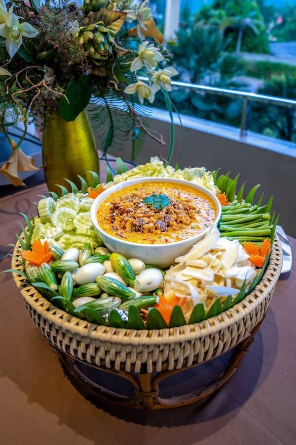 De traditionele Thaise Spaanse pepers kruidige saus riep Nam Prik in witte kom in het midden van plantaardige de wortelaubergine  stock afbeelding