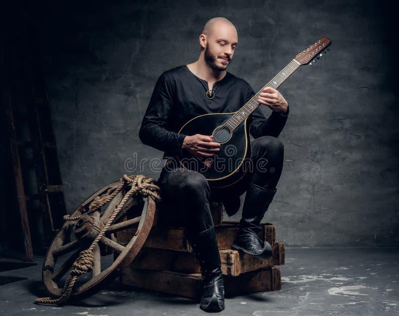 De traditionele volksmusicus gekleed in uitstekende Keltische kleren zit op een houten doos en speelt mandoline royalty-vrije stock foto's