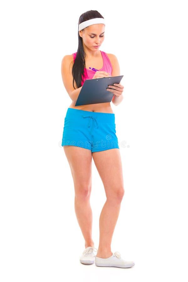 De trainer die van de geschiktheid nota's in opleidingsplan maakt stock foto's
