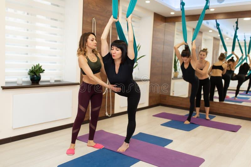 De trainer helpt om houding te houden terwijl vrouw die de uitrekkende oefeningen van de vliegyoga in gymnastiek doen Pasvorm en  royalty-vrije stock afbeeldingen
