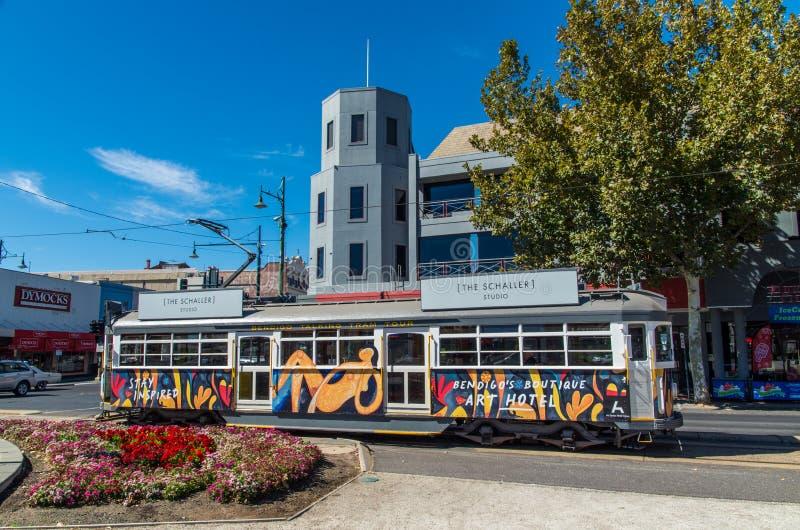De tram die van Bendigotramsporen langs Baarkleedwandelgalerij reizen in Bendigo stock foto