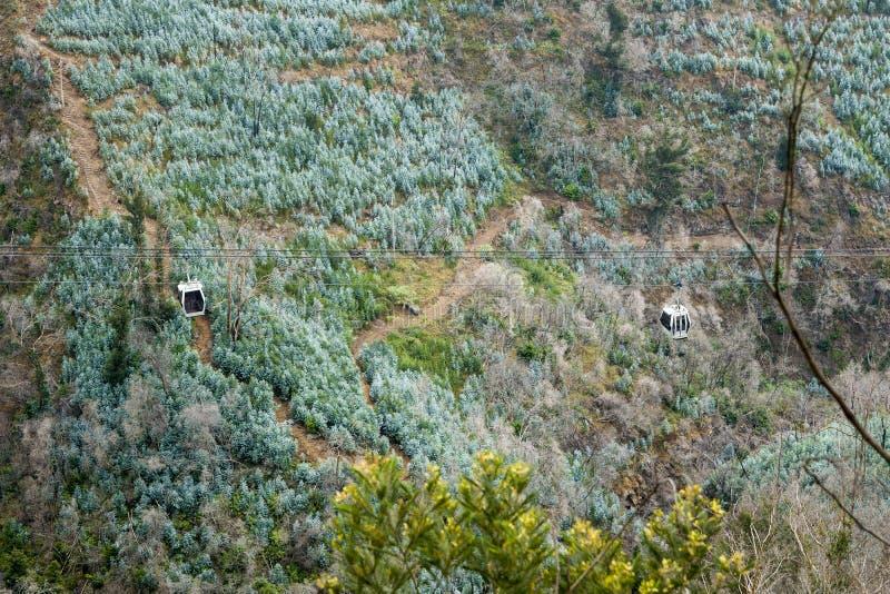De Tram van Airial van de Poort van de hel Twee kabelwagens worden afgeschilderd op een groene achtergrond van de berghelling De  royalty-vrije stock fotografie