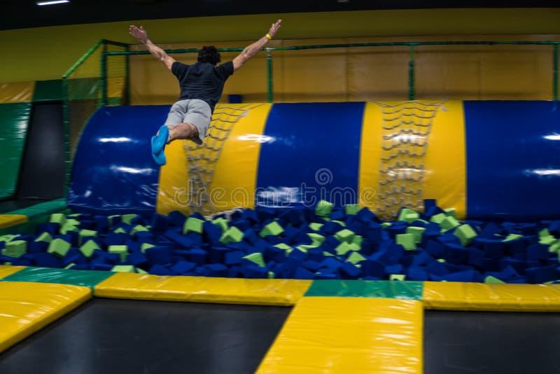 De trampolineverbindingsdraad voert acrobatische oefeningen op de trampoline uit stock afbeelding