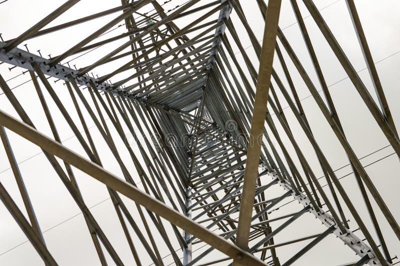 De transmissielijnen met hoog voltage van de torenmacht van de binnenkant aan de bodem stock afbeeldingen