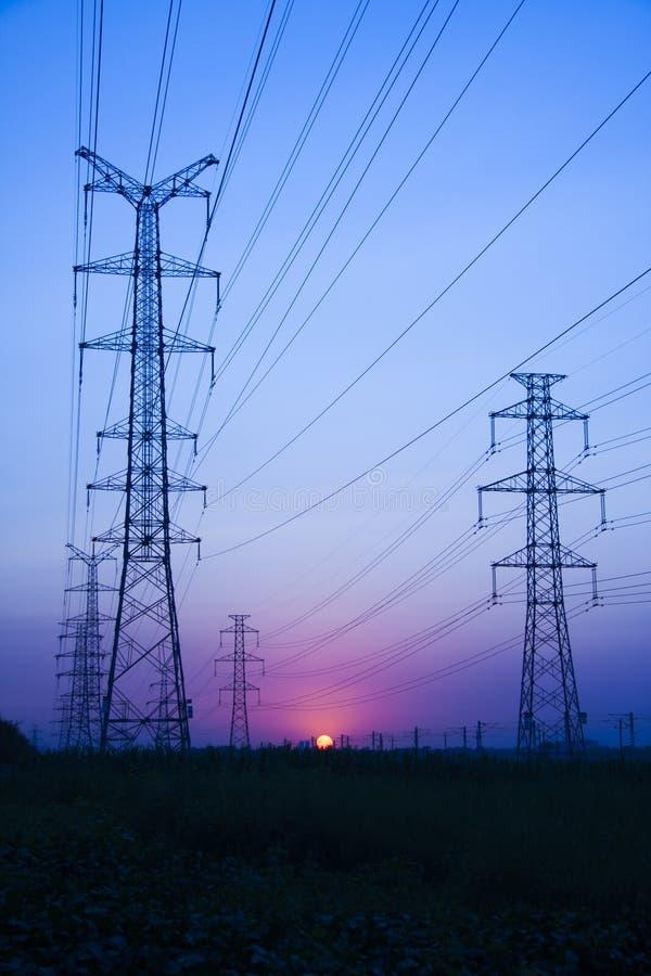 De transmissietoren van de hoogspanningselektriciteit bij zonsondergang stock foto's