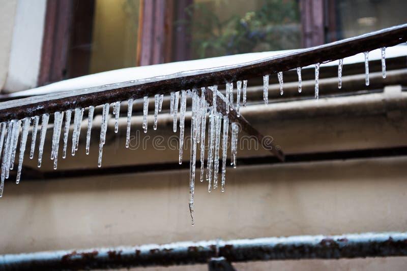 De transparante dunne ijskegels hangen onder het venster in de straat royalty-vrije stock afbeelding