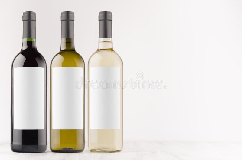 De transparante inzameling van wijnflessen -, groen, zwart met lege witte omhoog etiketten op witte houten raad, spot, exemplaarr stock afbeelding