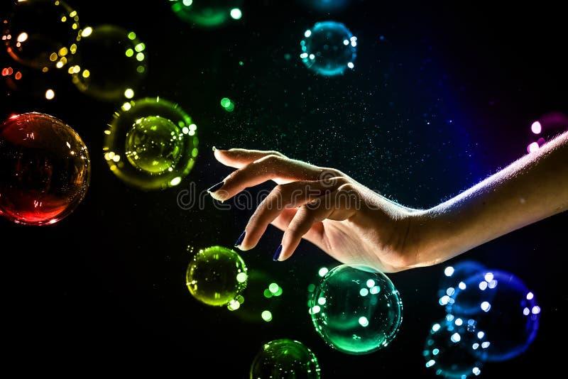 De transparante, iriserende die zeepbels op zwarte worden ge?soleerd stock foto