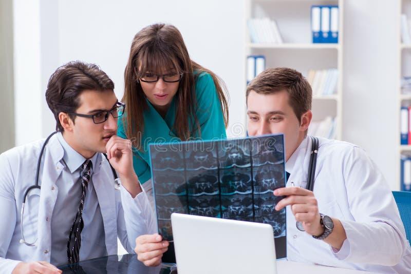 De tre doktorerna som diskuterar bildläsningsresultat av röntgenstrålebilden royaltyfria bilder