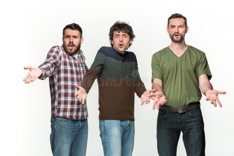 De tre männen är att le som ser kameran arkivfoton