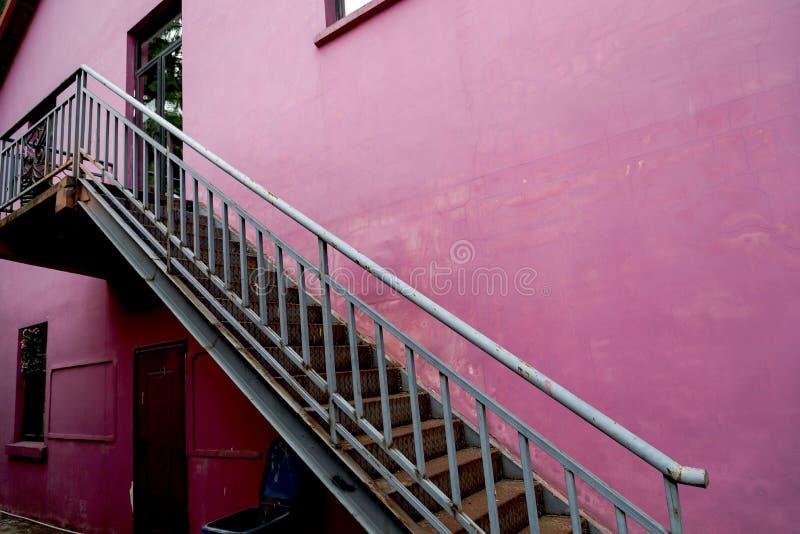 De treden op de roze muur royalty-vrije stock afbeeldingen