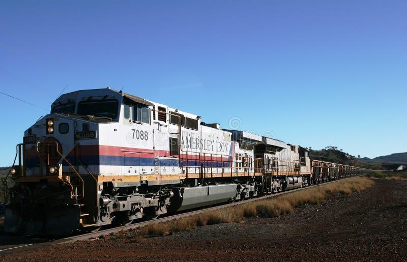 De trein van het Hamersleyijzererts op zijn manier van de mijn van Ondersteltom price aan Dampier-Haven stock afbeelding