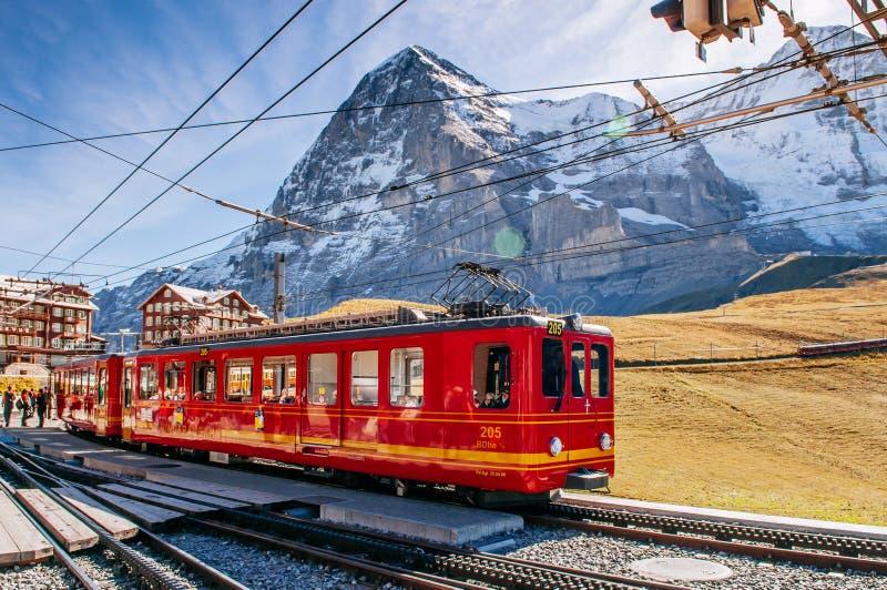 De trein van de Jungfrauspoorweg bij de post van Kleine Scheidegg met de piek van Eiger en Monch- stock foto