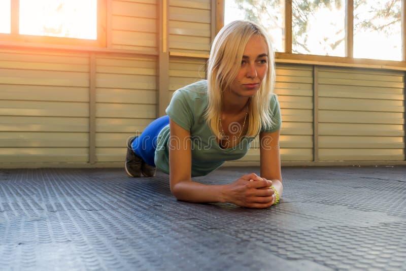 De treinen van het blondemeisje op een rubberdeklaag op de achtergrond van royalty-vrije stock foto's