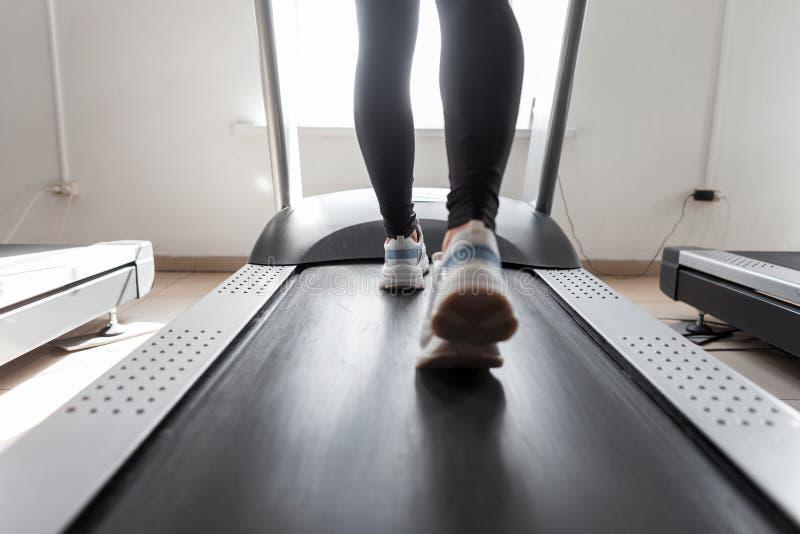 De treinen van de vrouwenbus op een tredmolen in een gymnastiek Meisjeslooppas op een tredmolen Sportenoefeningen voor gewichtsve royalty-vrije stock fotografie