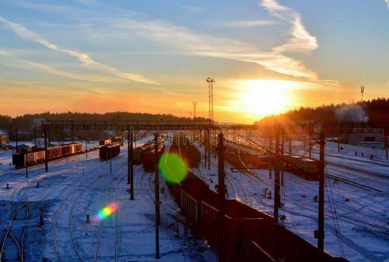 De treinplatform van de lading bij zonsondergang met container stock foto's