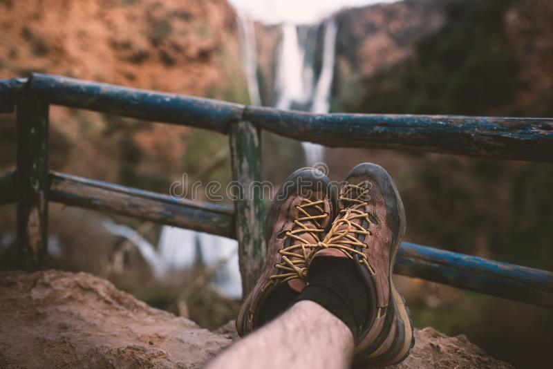 De trekkingsschoenen van Manin een aard van de dalingen van Marokko - Ouzod- Sluit omhoog van wandelingslaarzen tegen waterval royalty-vrije stock foto's