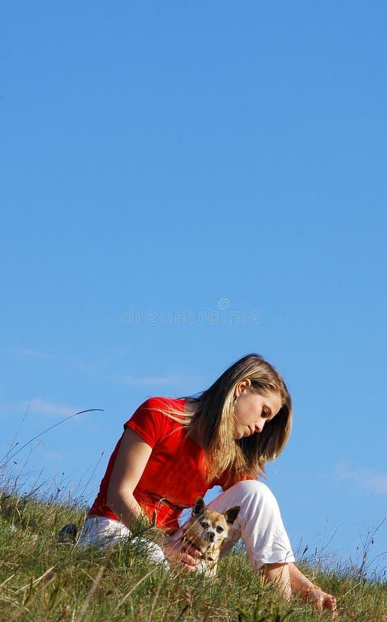 De tribune van de vrouw in gras stock fotografie