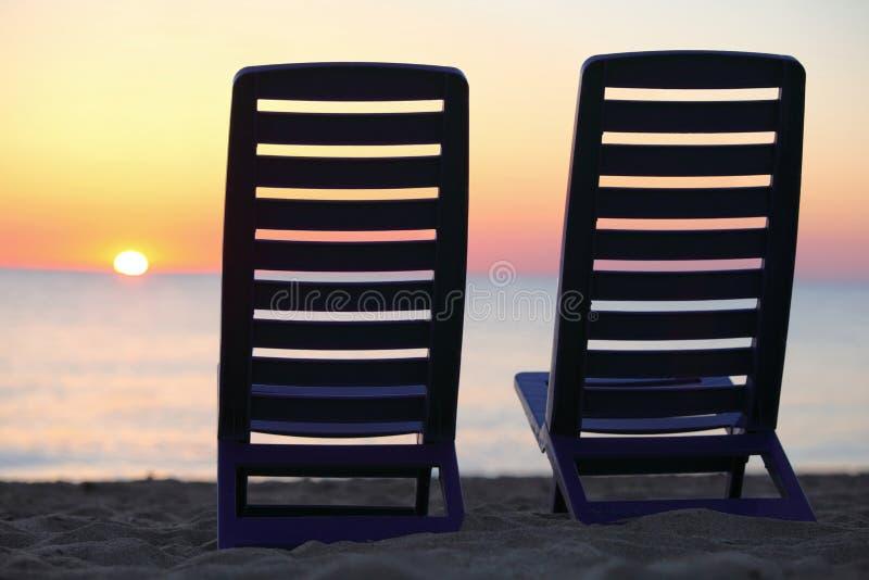De tribune van stoelen op strand dichtbij water stock afbeelding
